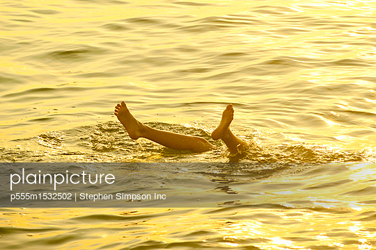 Feet of Caucasian boy sticking out of water - p555m1532502 by Stephen Simpson Inc