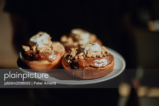 Barista carrying plate of chocolate doughnuts in cafe, cropped close up - p924m2098093 by Peter Amend