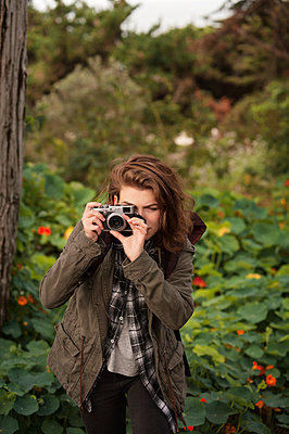 Beautiful hiker photographing through old-fashioned camera in forest - p1166m1154080 by Cavan Images