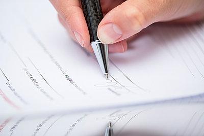 Woman signing documents - p300m1581041 von zerocreatives