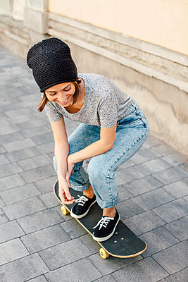 Smiling young female skate boarder on her skateboard - p300m949772f by Bonninstudio