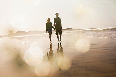 Full length of couple holding hands while walking at beach - p301m1148336 by Sven Hagolani
