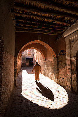 Local man dressed in traditional djellaba walking through archway in a street in the Kasbah, Marrakech, Morocco, North Africa, Africa - p871m1506645 by Lee Frost