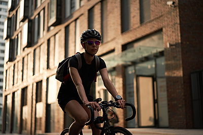 Woman cyclist in helmet on background of brick building in summer - p1630m2196906 by Sergey Mironov