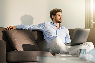 Man sitting on couch at home with laptop - p300m1549840 by Steve Brookland