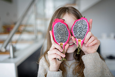 young girl is holding fresh, sliced dragon fruit pitahaya in front of her face - p300m2180687 von Epiximages