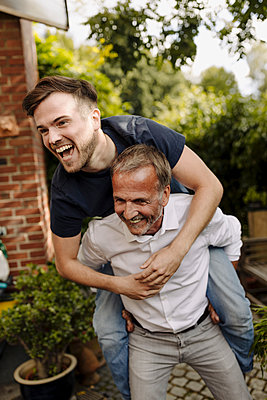 Happy father giving piggyback ride to laughing son in backyard - p300m2275013 by Gustafsson