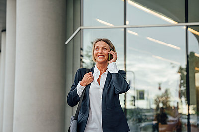 Smiling businesswoman talking on mobile phone at office park - p300m2294217 by Vasily Pindyurin