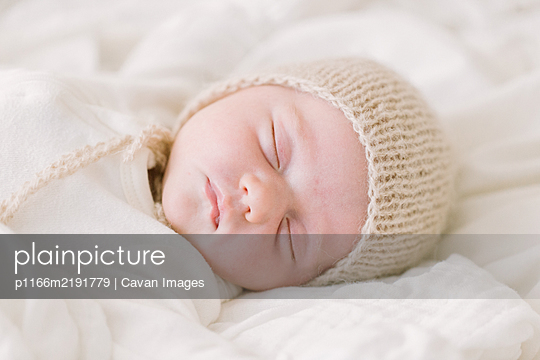 Newborn baby in knit bonnet sleeping on white bed - p1166m2191779 by Cavan Images
