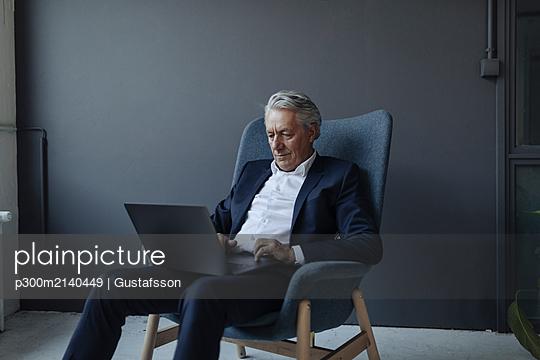 Senior businessman sitting in armchair using laptop - p300m2140449 by Gustafsson