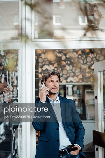 Mature businessman with hand in pocket talking on smart phone standing at doorway - p300m2293579 by Joseffson
