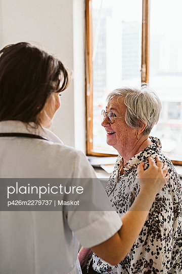 Female healthcare worker comforting senior patient at medical clinic - p426m2279737 by Maskot