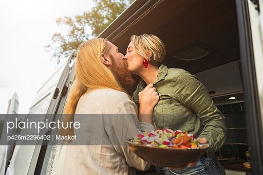 Young couple kissing while standing in motor home during vacation - p426m2296402 by Maskot