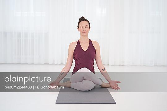 Woman practicing yoga in gym - p430m2244433 by R. Schönebaum