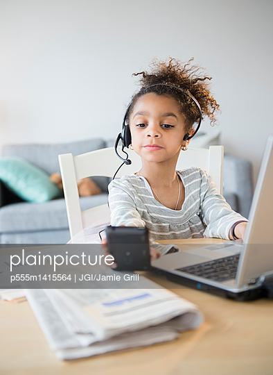 African American girl using headset, cell phone and laptop - p555m1415564 by JGI/Jamie Grill