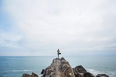 Woman exercising on rocks in sea - p1166m1210222 by Cavan Images