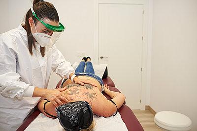 Masseur massages a woman's back. - p1166m2234859 by Cavan Images