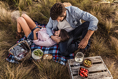 Affectionate couple having a picnic in the countryside - p300m2180841 by Floco Images