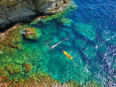 Spain, Catalonia, Costa Brava, Aerial view of woman in kayak near rocky coast - p300m2199014 by Veam