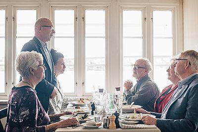 Senior friends talking in restaurant - p426m2149133 by Maskot