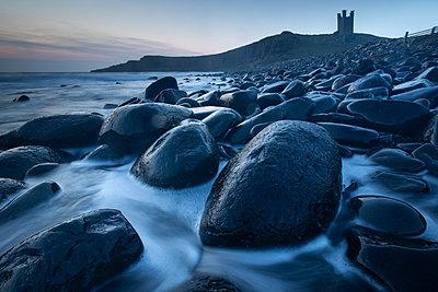 Tide swirling around black Dolerite boulders at Dunstanburgh Castle, Embleton Bay, Northumberland, England, United Kingdom - p871m2113716 by David Speight