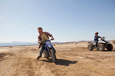 Man riding dirt bike in desert - p924m768496f by Raphye Alexius