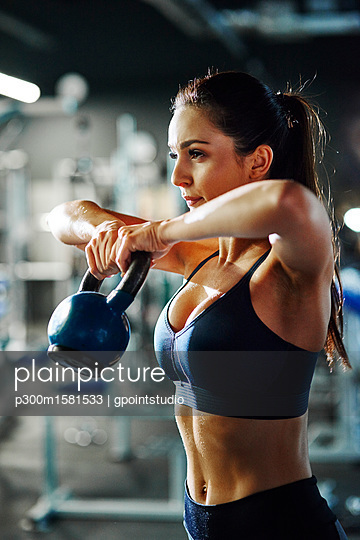 Woman exercising with a kettlebell in gym - p300m1581533 von gpointstudio