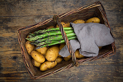 Organic green asparagus and organic potatoes in wickerbasket on wood - p300m2005524 von Larissa Veronesi