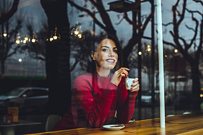 Smiling young woman with cup of coffee behind windowpane in a cafe - p300m2102085 by Aitor Carrera Porté