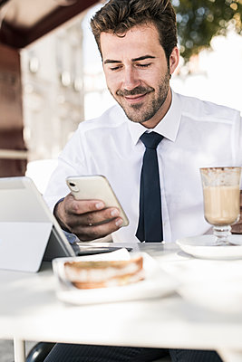 Young businessman using tablet and mobile phone at a cafe in the city, Lissabon, Portugal - p300m2144885 von Uwe Umstätter