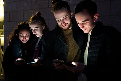 Friends looking at illuminated smartphones in the dark - p300m2170191 by Francesco Buttitta