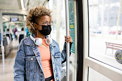 Mid adult woman wearing protective face mask standing while looking through tram window - p300m2276431 by Rafael Fernandez Torres