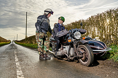 Senior male motorcyclist talking to grandson sitting on motorcycle on rural roadside - p429m1226738 by GS Visuals