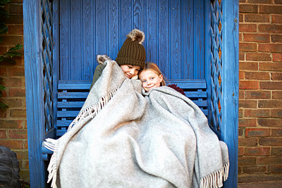 Siblings wrapped in blanket resting on arbour bench - p429m1227143 by Peter Muller