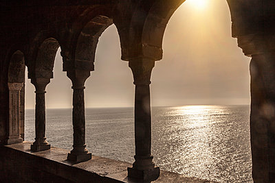 Sunlight on sea, viewed through arches, Portovenere, Cinque Terre, Liguria, Italy - p429m1450646 by WALTER ZERLA