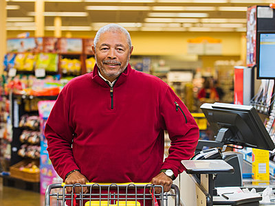 African American customer at grocery store checkout - p555m1453321 by Erik Isakson