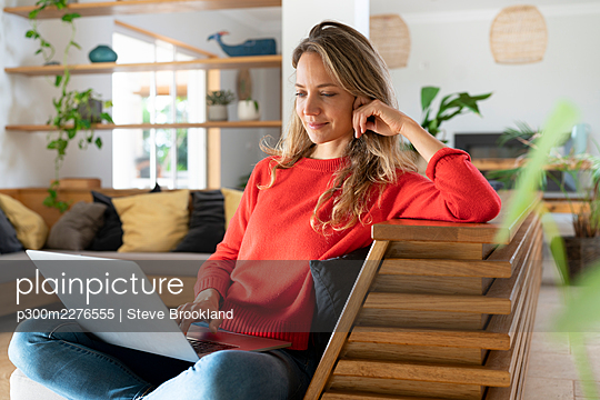 Woman using laptop sitting in living room at home - p300m2276555 by Steve Brookland