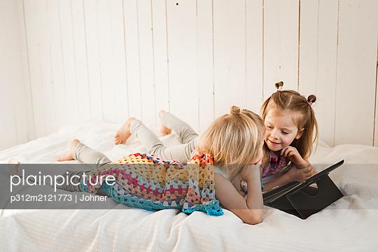 Girls using digital tablet - p312m2121773 by Johner