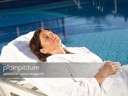 Aeltere Frau in weissem Bademantel am Pool  - p6430319f von senior images RF