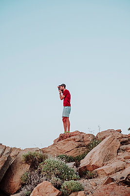 A photographer taking photos on the top of Guajara Peak, Tenerife - p1166m2131202 by Cavan Images