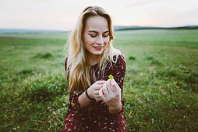 Smiling woman holding flower in field - p1427m2186496 by Oleksii Karamanov