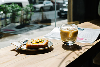 Cold brew coffee and cake on table at coffee shop - p300m2226606 by Xavier Lorenzo