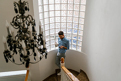 Man having coffee while using mobile phone standing on staircase at home - p300m2265825 by Ezequiel Giménez