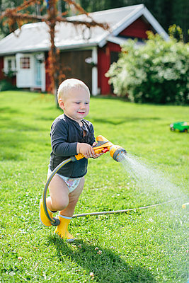 Boy with garden hose - p312m1121568f by Anna Rostrom