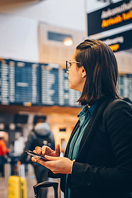 Mid adult businesswoman using mobile phone while standing in airport - p426m1580059 by Maskot