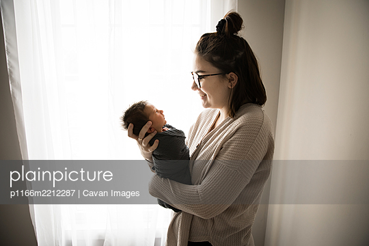 Gen Z Hipster Mom Smiles at Swaddled Newborn in Front of Window - p1166m2212287 by Cavan Images