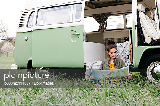 Young woman studying map, sitting in the grass, in front of her camper - p300m2114357 von Epiximages
