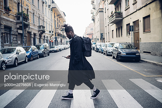 Fashionable man using mobile phone while crossing road in city - p300m2276605 by Eugenio Marongiu