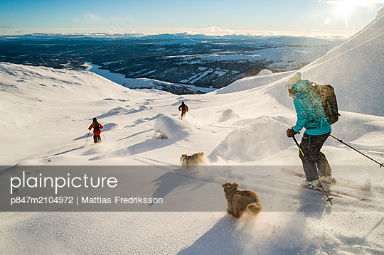 Skiers and dogs enjoying early season powder snow on Åreskutan, Åre, Sweden. - p847m2104972 by Mattias Fredriksson