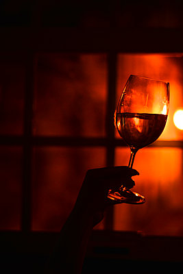 Hand holding wine glass against red light - p1695m2290955 by Dusica Paripovic